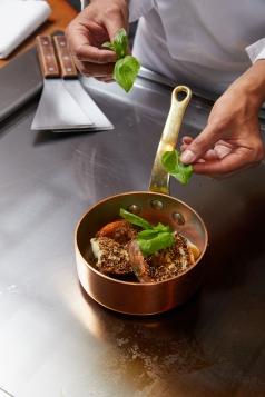 「胡椒伊勢龍蝦」發想自台灣的胡椒蝦,將鮮活龍蝦蘸取胡椒後於鐵板上煎出辛辣香氣,置入銅鍋中加入雞高湯及蘿勒葉拌炒。